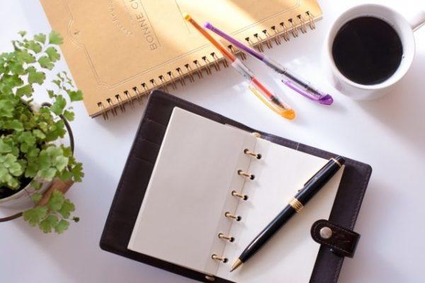 机の上の筆記用具とコーヒー