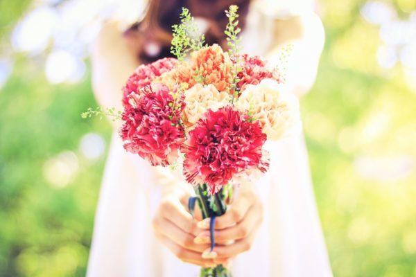 カーネーションの花束を持つ女性