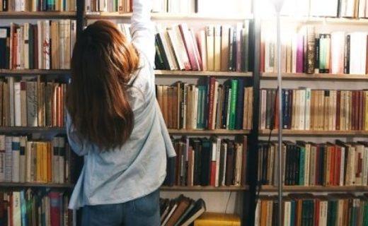 本棚に手を伸ばす女性
