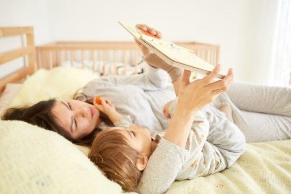 ベットで絵本を読み聞かせる母と子