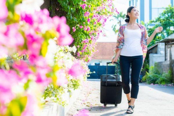 花の道でキャリーを引く女性