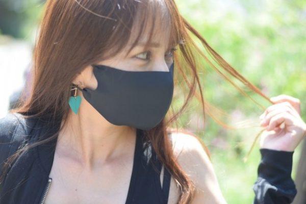 黒いマスクをつける女性が髪をいじる